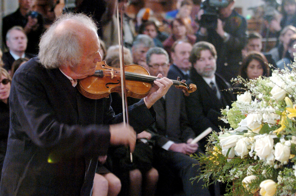 Israeli violinist Ivry Gitlis, ambassador to the UNESCO, plays at the funeral ceremony of Oscar-winning British actor and play-writer, Sir Peter Ustinov, in Geneva, Switzerland in 2004. (Martial Trezzini/Pool Photo via AP, File)