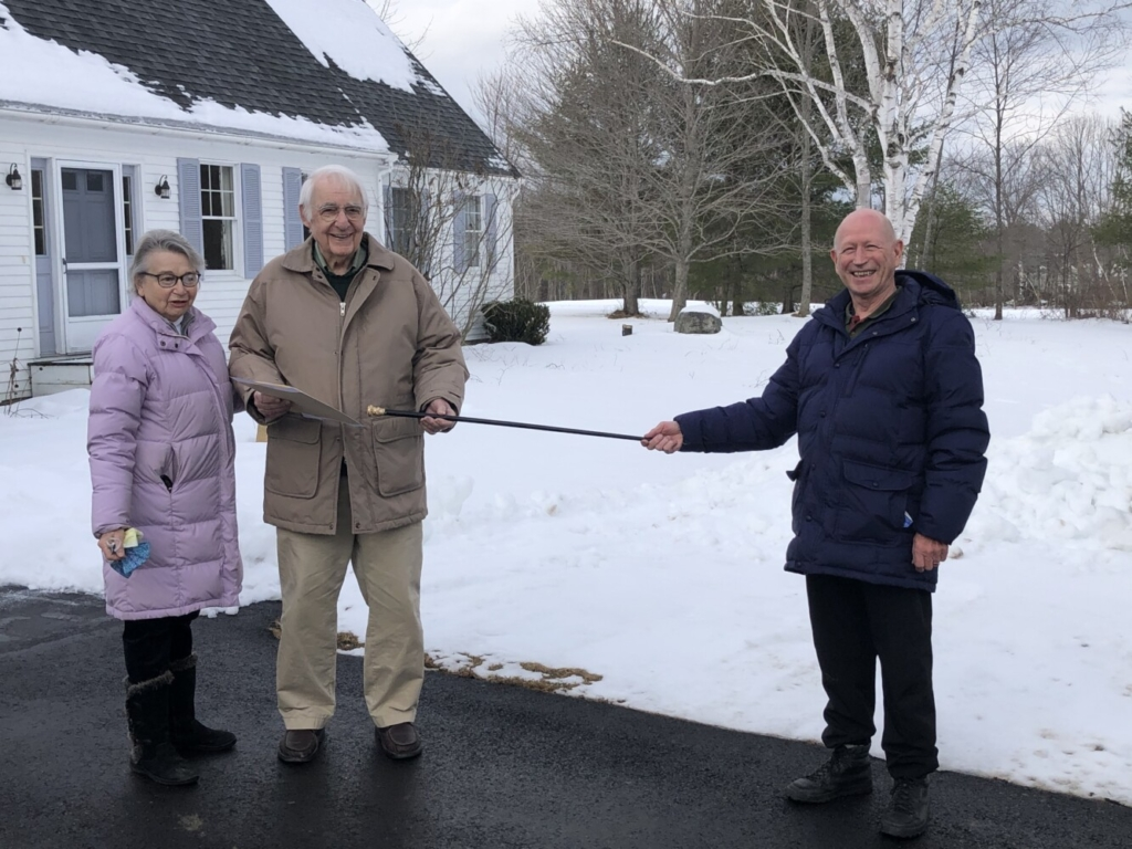 """Don Welsh, right, Selectboard chairperson, presents the Wayne Cane to Lincoln Ladd on Dec. 22 at his residence, """"Sunshine Hill"""" in Wayne, with his wife Gloria by his side."""
