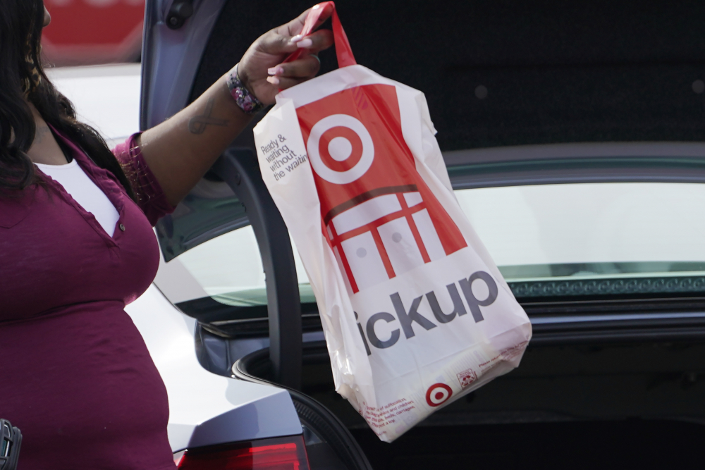 A Target employee places a curbside pickup purchase into the trunk of a customer's car in Jackson, Miss. Many struggling retailers are stepping up discounts while heavily promoting curbside pickup as a way to get shoppers, worried about being infected with  the virus,  to visit their stores.  (AP Photo/Rogelio V. Solis)