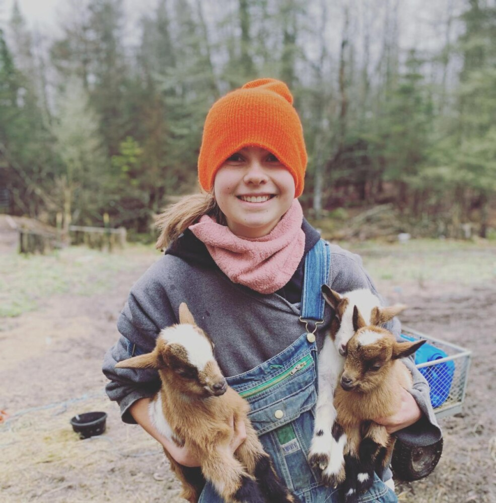 Margaret Mae Reilich holds goats at Painted Pepper Farm in Steuben. The farm will use the grant to invest in a farm stand that will enable safe and easy on-farm pick up.