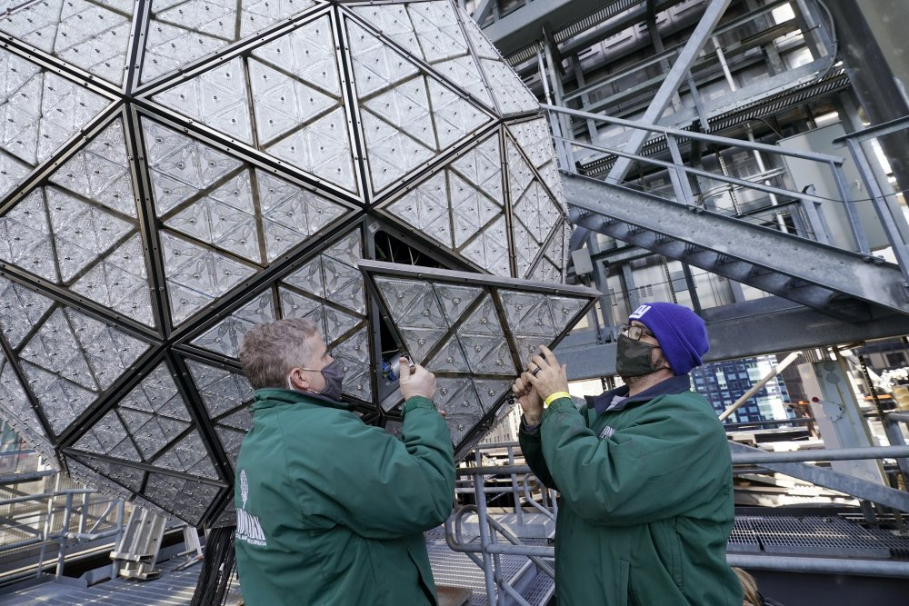 Workers install a panel of Waterford crystal triangles on the Times Square New Year's Eve ball, Sunday in New York, in preparation for a pandemic-limited celebration.