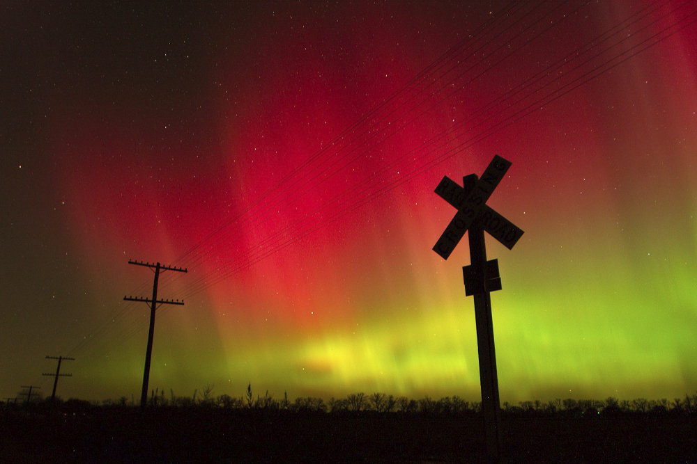 The aurora borealis lights up the sky northwest of Lawrence, Kan., in 2004. The phenomenon, also called northern lights, occurs when electrically charged particles from the sun enter the earth's atmosphere.