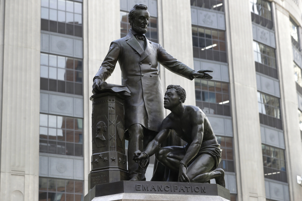 The statue that depicts a freed slave kneeling at President Abraham Lincoln's feet rests on a pedestal in Boston.