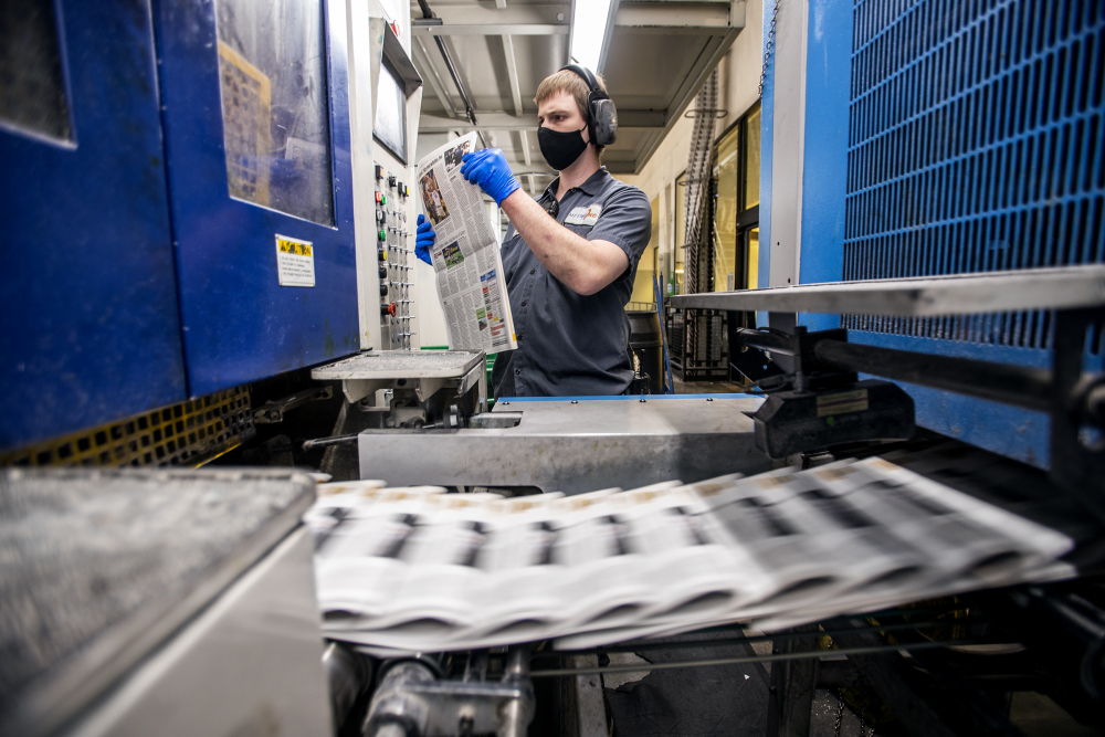 A press worker checks a newspaper as the last daily edition of the Deseret News is printed at the MediaOne building in West Valley City, Utah, on Wednesday.