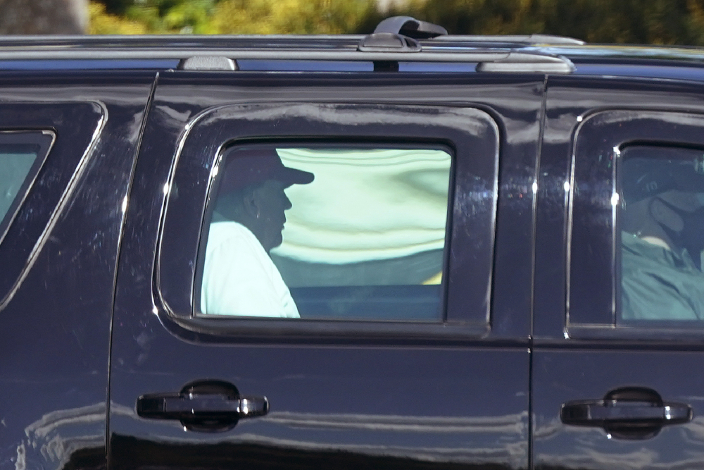 President Trump rides in a motorcade vehicle as he departs Trump International Golf Club on Sunday in West Palm Beach, Fla.
