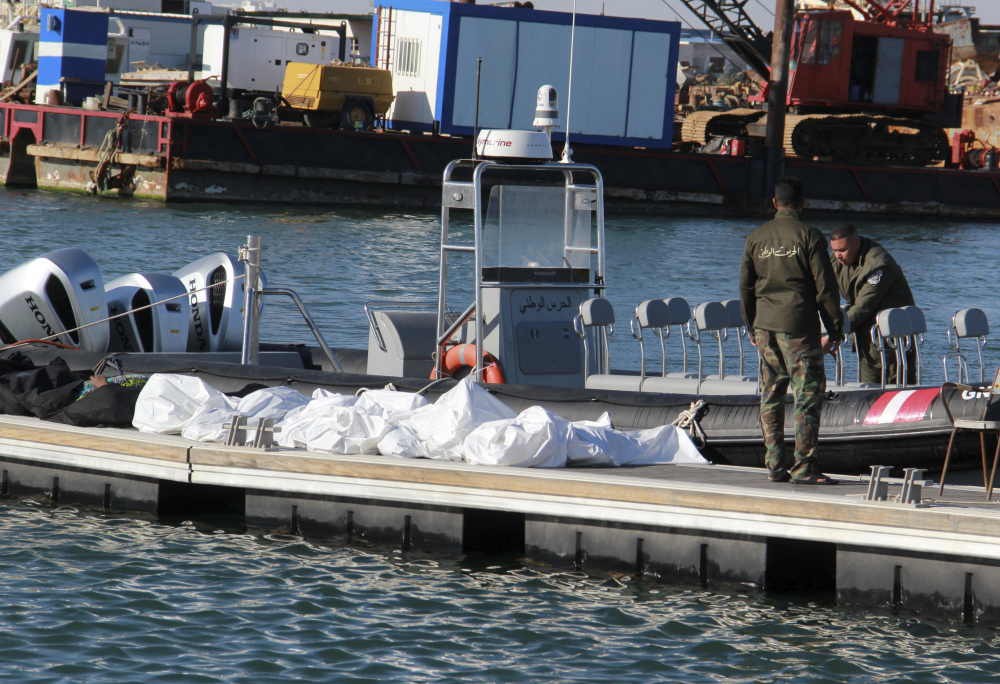 Tunisian coast guards stand next to the bodies of migrants in the port of Sfax on Thursday.