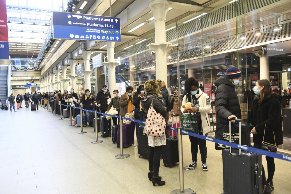 People at St Pancras station in London wait to board the last train to Paris on Sunday.  British Prime Minister Boris Johnson said Saturday that holiday gatherings can't go ahead and non-essential shops must close in London and much of southern England, leading to a rush of people looking to leave the region.