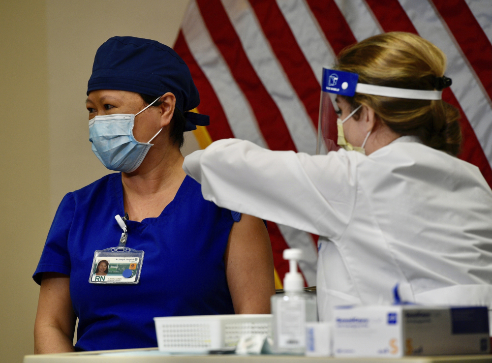 Nurse Song Lee looks away as she gets a dose of the Pfizer-BioNTech COVID-19 vaccine from nurse practitioner Christie Aiello at Providence St. Joseph Hospital in Orange, Calif., Wednesday, Dec. 16, 2020. (Jeff Gritchen/The Orange County Register via AP)