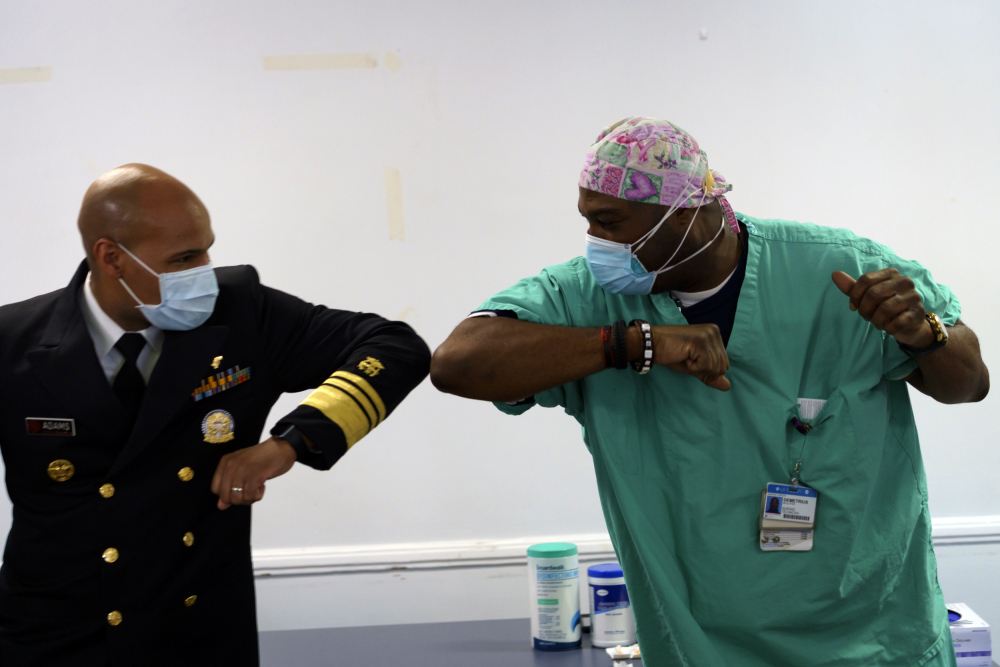Surgeon General of the U.S. Jerome Adams, left, elbow-bumps Emergency Room technician Demetrius Mcalister after Mcalister got the Pfizer COVID-19 vaccination at Saint Anthony Hospital in Chicago, on Tuesday.