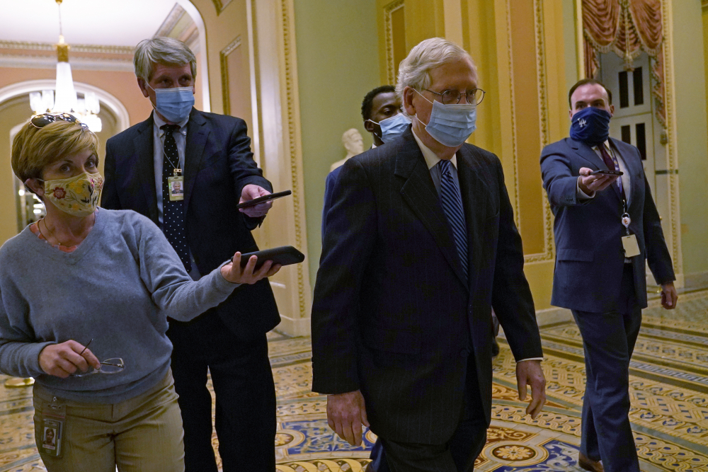 Senate Majority Leader Mitch McConnell of Ky., walks past reporters on Capitol Hill in Washington, Tuesday, Dec. 15.