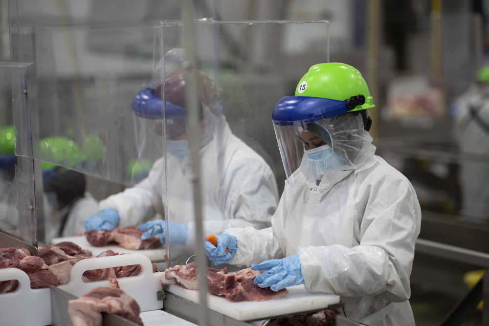 Workers inside Smithfield Foods' pork processing plant in Sioux Falls, South Dakota, wear protective gear and are separated by plastic partitions as they carve up meat in May.