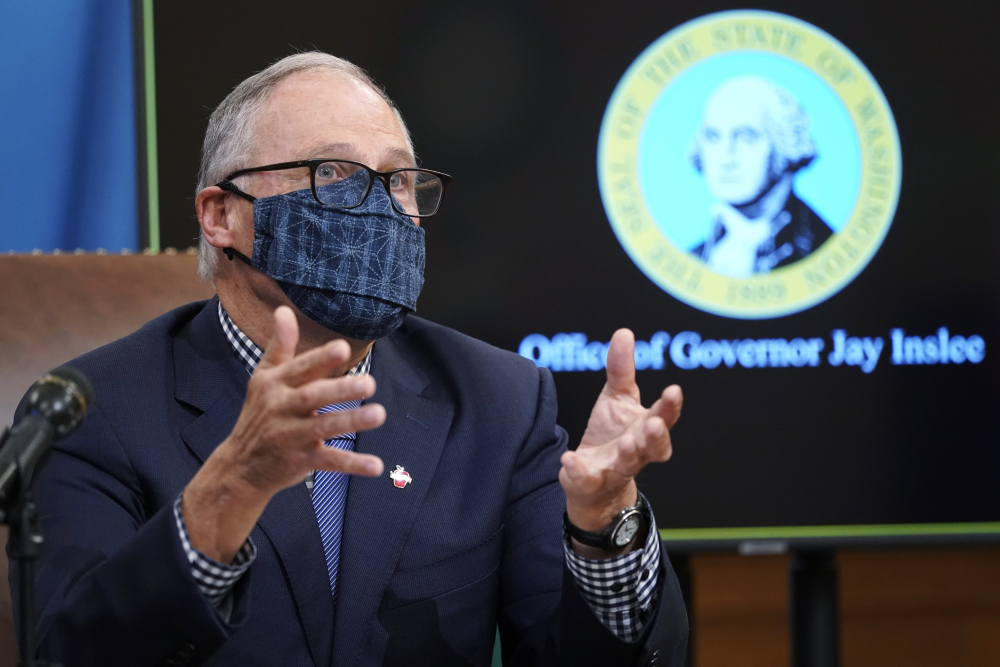 Washington Gov. Jay Inslee talks to reporters at the Capitol in Olympia, Wash., on Dec. 17.  State lawmakers across the country will be convening in 2021 with the continuing COVID-19 pandemic rippling through much of their work — and even affecting the way they work.