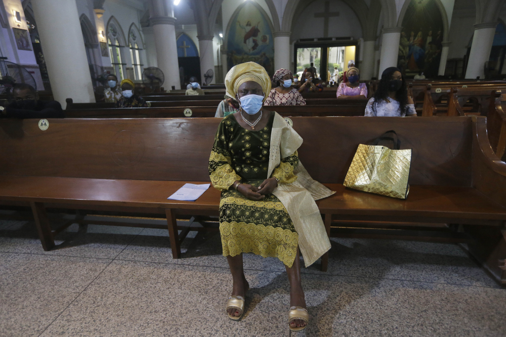 Parishioners, wearing face masks to protect against coronavirus, attend a morning Christmas Mass at Holy Cross Cathedral in Lagos, Nigeria. Africa's top public health official says another new variant of the coronavirus appears to have emerged in Nigeria, but further investigation is needed. The discovery could add to new alarm in the pandemic after similar variants were announced in recent days in Britain and South Africa and sparked the swift return of travel restrictions.