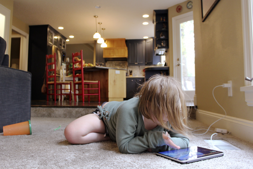 Lizzie Dale sprawls on the floor to play games on an iPad as her siblings work on school work in the kitchen behind her in their home in Lake Oswego, Ore., on Oct. 30. In Oregon, one of only a handful of states that has required a partial or statewide closure of schools in the midst of the COVID-19 pandemic, parents in favor of their children returning to in-person learning have voiced their concerns and grievances using social media, petitions, letters to state officials, emotional testimonies at virtual school board meetings and on the steps of the state's Capitol.