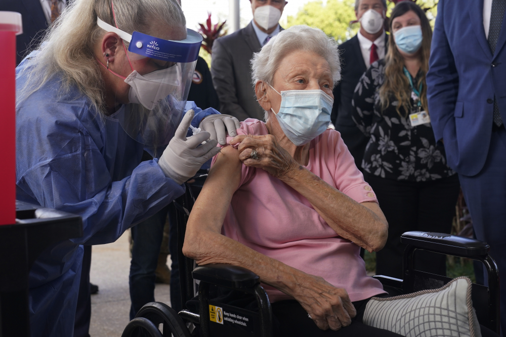 Nurse Christine Philips administers the Pfizer vaccine to Vera Leip, 88, a resident of John Knox Village, on Wednesday in Pompano Beach, Fla. Nursing home residents and health care workers in Florida began receiving the Pfizer vaccine this week.