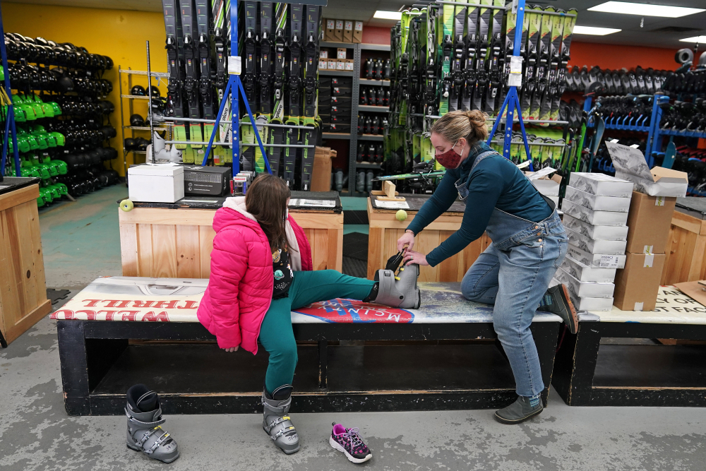 Meredith Hopkins, right, helps fit ski boots on Makenna Houghton at the ski shop at McIntyre Ski Area on Wednesday in Manchester, N.H.