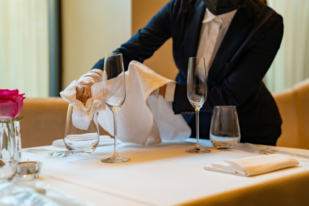 A worker wearing a protective mask cleans glassware at Jungsik restaurant in New York on Sept. 30. Included in Congress' measure for economic relief is a favorite of President Donald Trump: a write-off for wining and dining business clients.