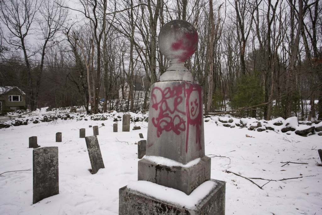 Spray painted words and a picture mar a gravestone at the Roberts-Wakefield Cemetery in Waterboro, The York County Sheriff's Office is investigating the vandalism that defaced nearly a dozen grave markers in the historic cemetery.