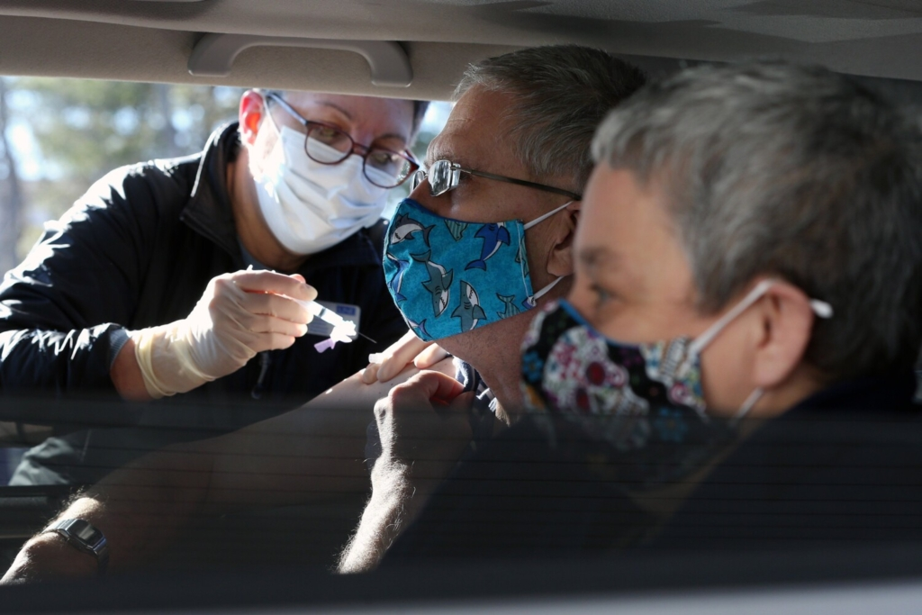 Greg Barlag, center, a client at Community Living, receives a first dose of a coronavirus vaccine Monday in Brunswick. About 200 peeopl with intellectual disabilities and their service providers received the vaccine at a drive-thru vaccination clinic.
