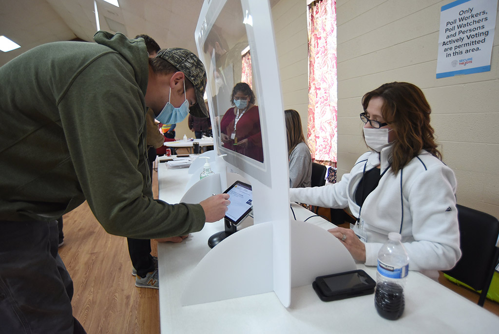 Poll worker Jennifer Jones signs in Taylor Ledford at the polling place at Dawnville United Methodist Church in Dawnville, Ga., on Tuesday.