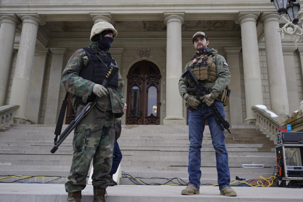 Men with a shotgun and a rifle stand on the steps at the state Capitol after a rally in support of President Trump in Lansing, Mich., on Wednesday.