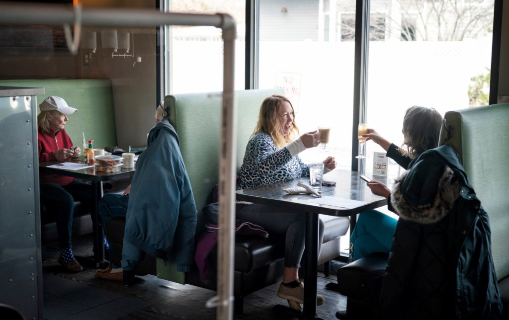 Dawn Kaphingst, left, toasts to her cousin Jane Murray's birthday as the two get together for the first time since summer at Longfellow Grill in Minneapolis on Monday, the first day restaurants were allowed to reopen, at 50 percent capacity.