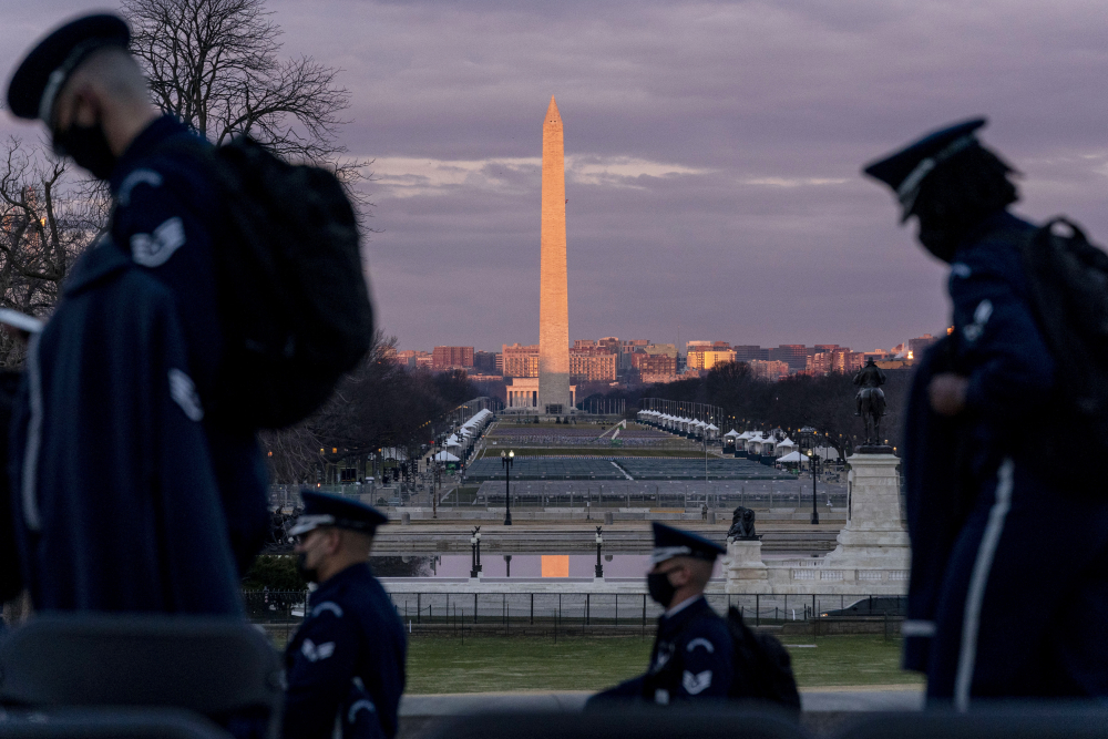 The Washington Monument and the National Mall are visible as members of the U.S. Air Force Honor Guard walk along the West Front of the U.S. Capitol at the site of the 59th Presidential Inauguration in Washington on Monday. (AP Photo/Andrew Harnik)