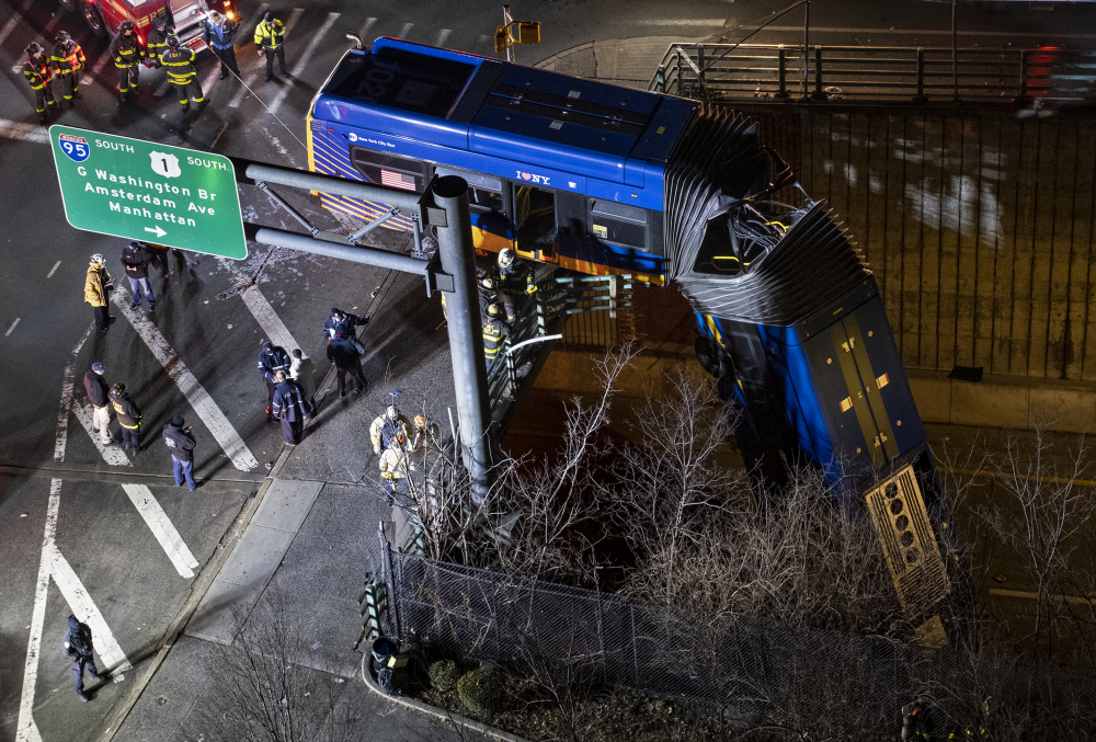 A bus in New York City that careened off a road in the Bronx neighborhood of New York is left dangling from an overpass Friday.