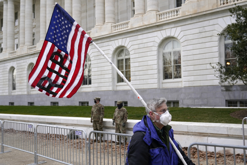 A protester walks past the Russell Senate Office Building on Capitol Hill in Washington on Friday. There may be volatility ahead for the Republican Party as it braces for political fallout from the riot that Trump incited.