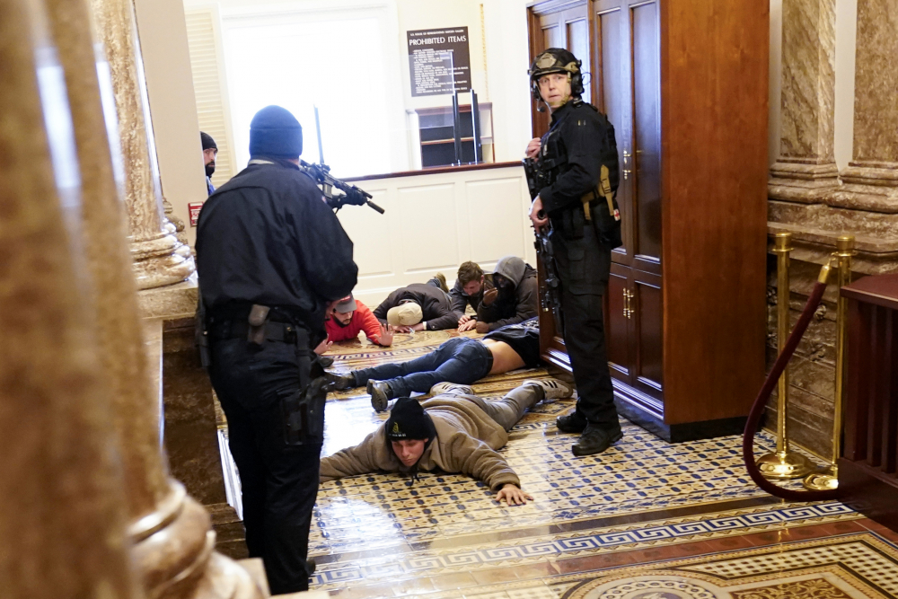 U.S. Capitol Police hold protesters at gun-point near the House Chamber on Wednesday inside the U.S. Capitol in Washington.