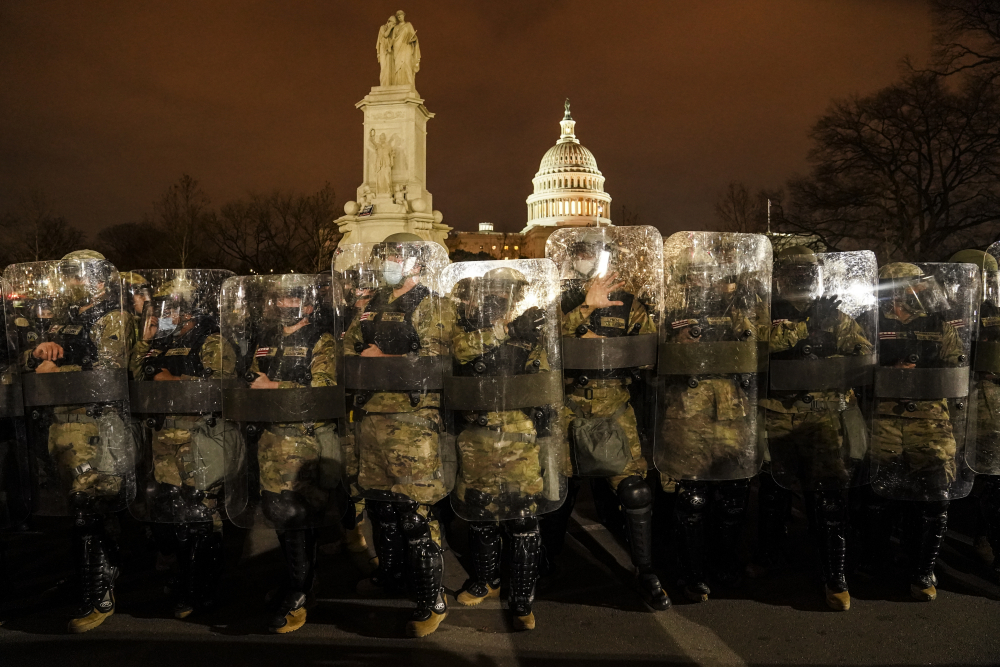 District of Columbia National Guard members stand outside the Capitol on the night of Jan. 6, after a day of rioting protesters.