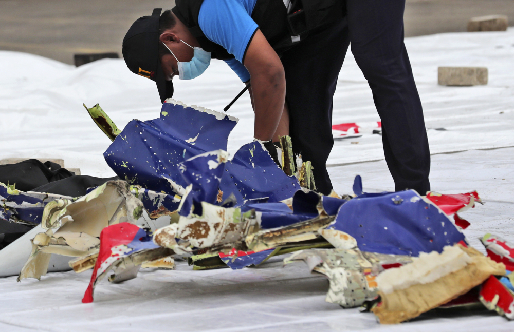 An investigator with the Indonesian National Transportation Safety Committee inspects parts of Sriwijaya Air Flight 182 that crashed in the waters off Java Island, at Tanjung Priok Port in Jakarta, Indonesia, on Sunday.