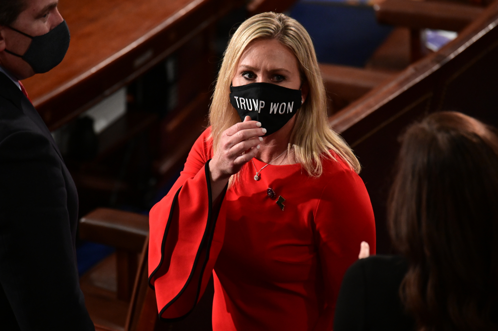 """Rep. Marjorie Taylor Greene, R-Ga., wears a """"Trump Won"""" face mask as she arrives on the floor of the House to take her oath of office on opening day of the 117th Congress at the U.S. Capitol on Sunday. Taylor Greene is one of a dozen elected officials who seek to overturn presidential election results."""