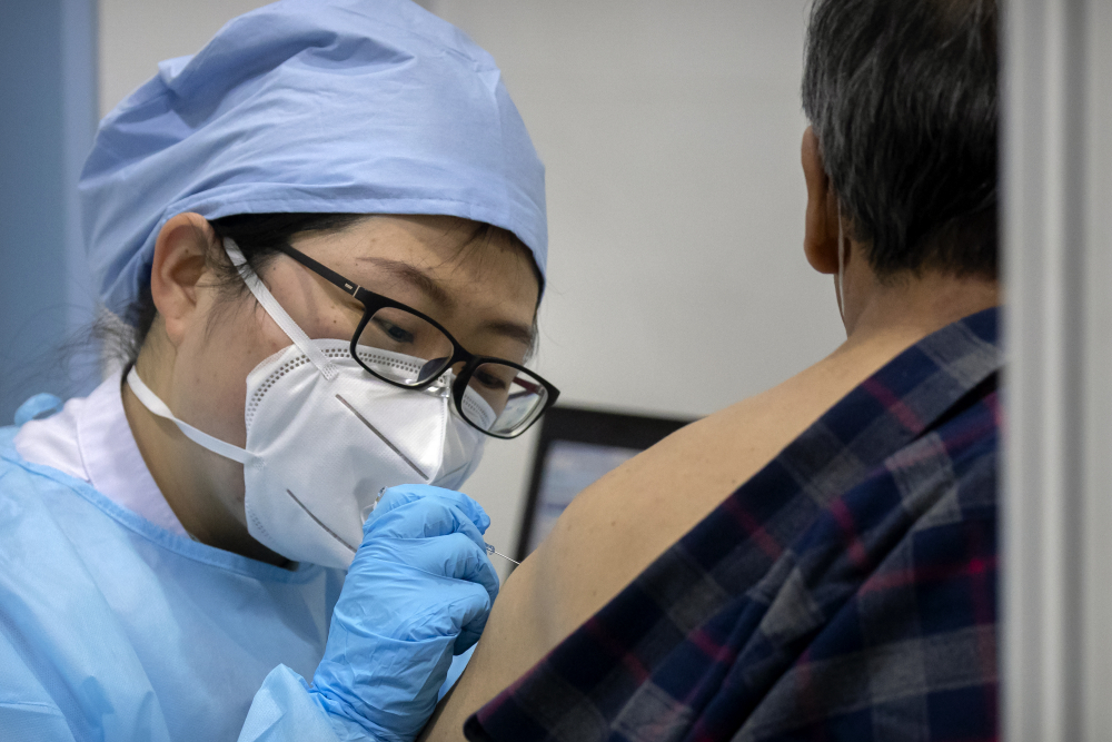 A medical worker gives a coronavirus vaccine shot to a patient in Beijing on Friday.