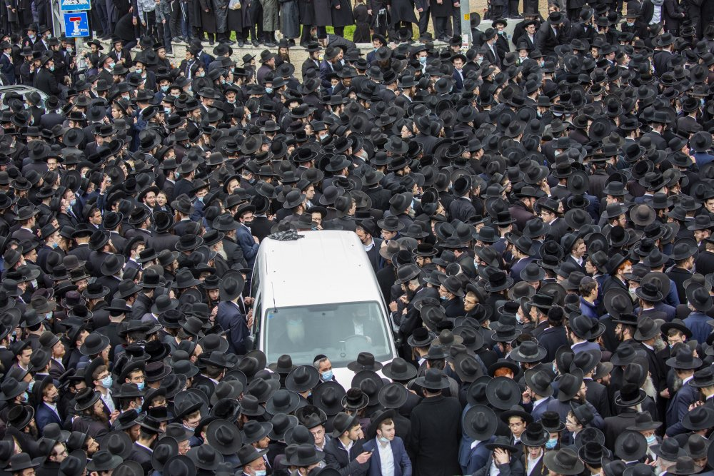 Thousands of ultra-Orthodox Jews participate in the funeral for prominent rabbi Meshulam Soloveitchik in Jerusalem on Sunday.  Israel restricts outdoor gatherings to 10 people. (AP Photo/Ariel Schalit)