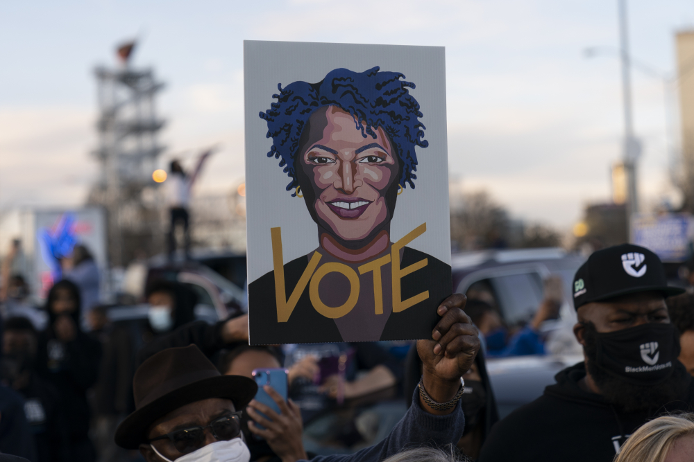People in the crowd hold up an image of Stacey Abrams as President-elect Joe Biden speaks in Atlanta, Monday to campaign for Georgia Democratic candidates for U.S. Senate, Rev. Raphael Warnock and Jon Ossoff.