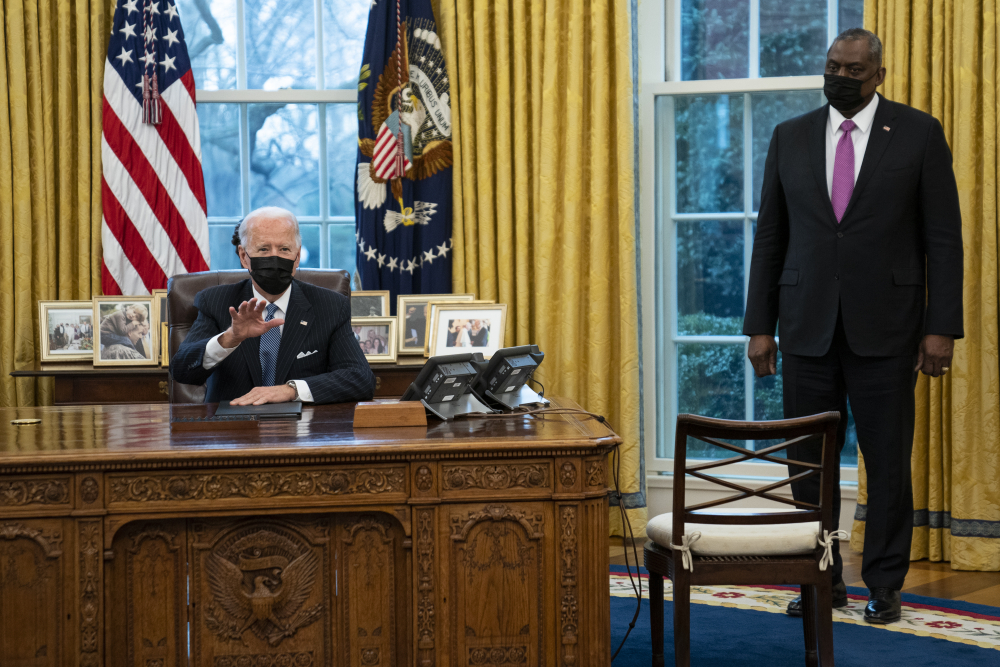 Secretary of Defense Lloyd Austin listens as President Joe Biden speaks before signing an Executive Order reversing the Trump era ban on transgender individuals serving in military, in the Oval Office of the White House, Monday, Jan. 25, in Washington.