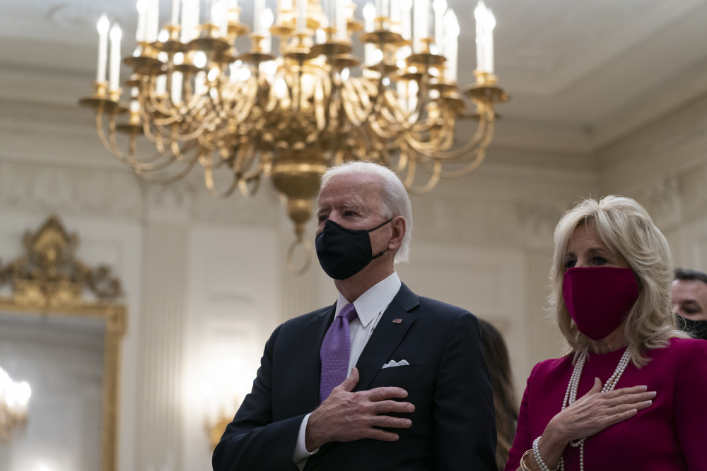 President Biden, accompanied by first lady Jill Biden, places his hand over his heart during a performance of the national anthem, during a virtual Presidential Inaugural Prayer Service in the State Dining Room of the White House on Thursday.