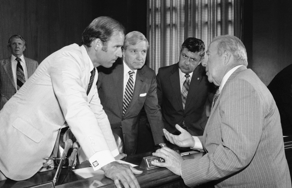 In this July 13, 1982, file photo Secretary of State designate George Shultz, right, speaks with members of the Senate Foreign Relations Committee. From left are Sen. Joseph Biden, D-Del.; Sen. Charles Percy, R-Ill., chairman of the panel, and Sen. Edward Zorinsky, D-Neb. (AP Photo/Ira Schwarz, File)