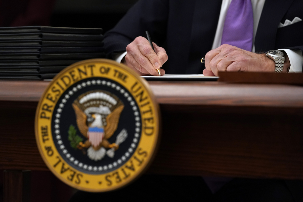 President Biden signs executive orders Thursday at the White House.