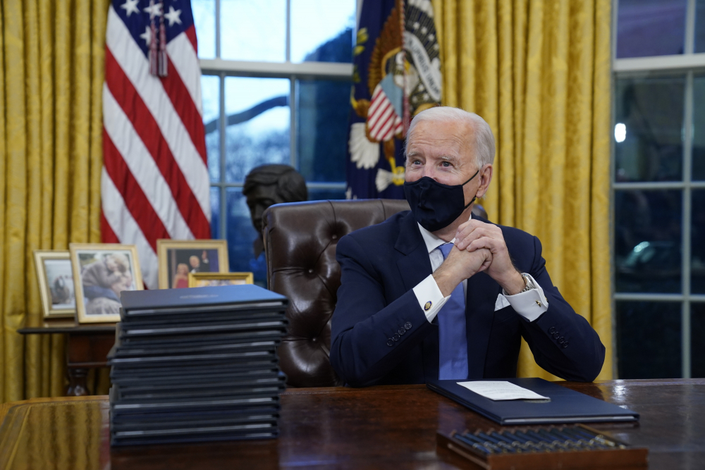 President Biden waits to sign his first executive order in the Oval Office of the White House on Wednesday in Washington.