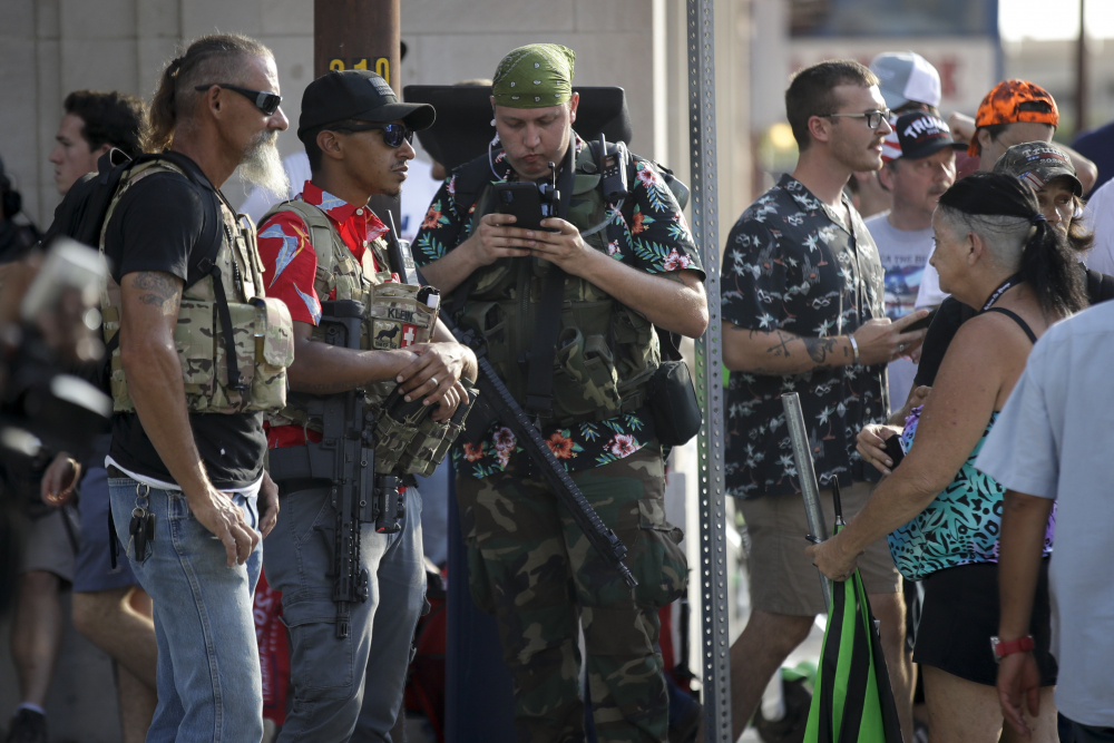 Gun-carrying men wearing Hawaiian print shirts associated with the boogaloo movement watch a demonstration near where President Trump had a campaign rally in Tulsa, Okla., in June. The anti-government promotes violence and a second U.S. civil war.