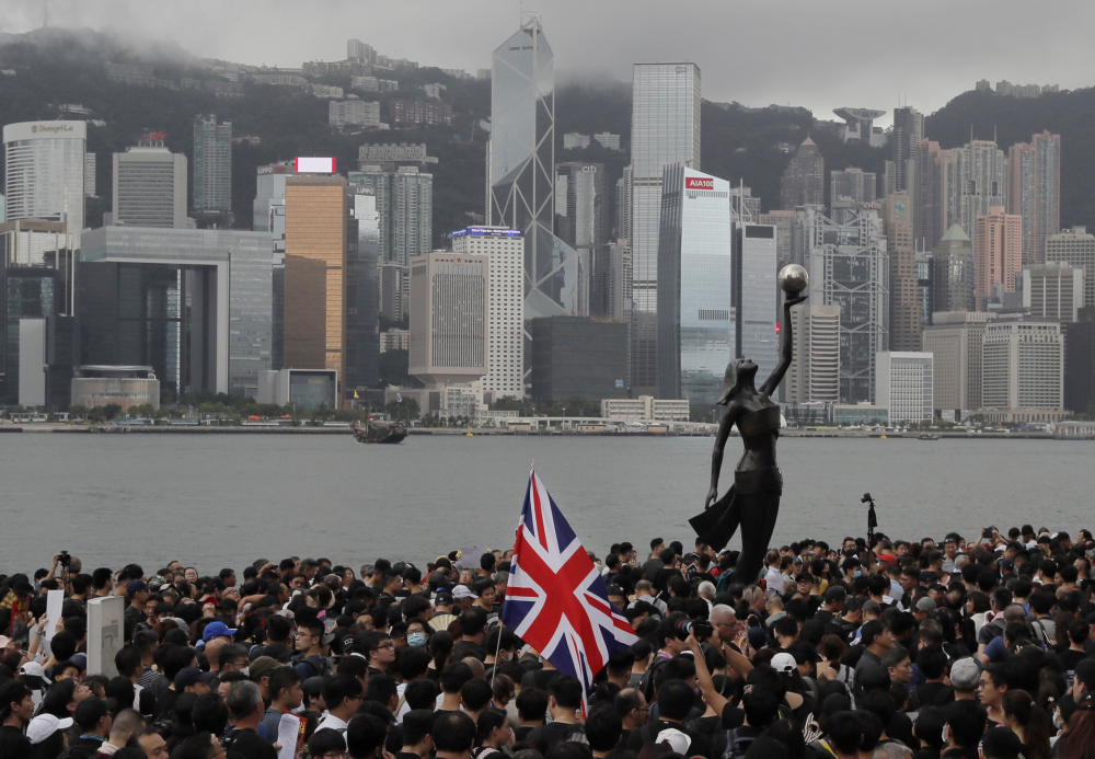 Thousands of protesters carrying the British flag march near the harbor of Hong Kong on July 7, 2019. The British government estimates more than 300,000 Hong Kongers will take up the offer of extended residency rights in the United Kingdom in the next five years.