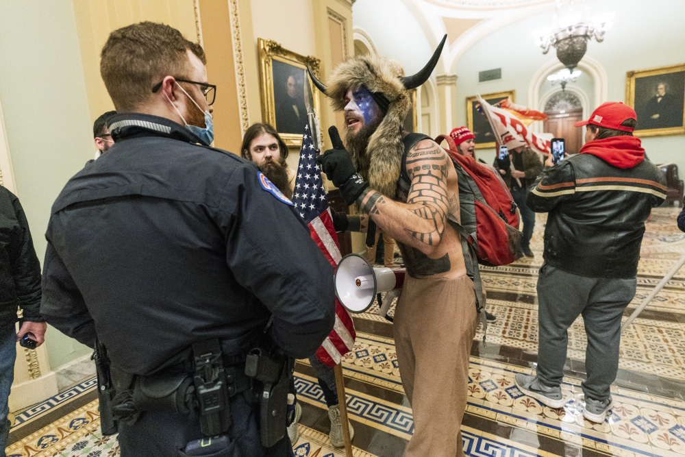 Jacob Anthony Chansley, who also goes by the name Jake Angeli, is shown during the Capitol riot on Jan. 6. Prosecutors say he left a note threatening Vice President Mike Pence, who had been evacuated from the Senate chamber.