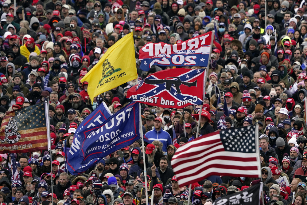 Supporters listen as President Trump speaks Jan. 6 while a Confederate-themed and other flags flutter in the wind during a rally in Washington.
