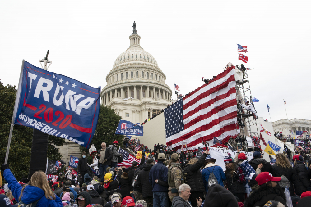 Supporters of President Trump stand outside the U.S. Capitol in Washington on Jan. 6 before storming the building. Lawyers interviewed by the Associated Press agreed that it would be stretch to try to put Trump or lawyer Rudolph Giuliani on trial for sedition for what some have criticized as incendiary rhetoric at the rally preceding the mob attack on the Capitol.