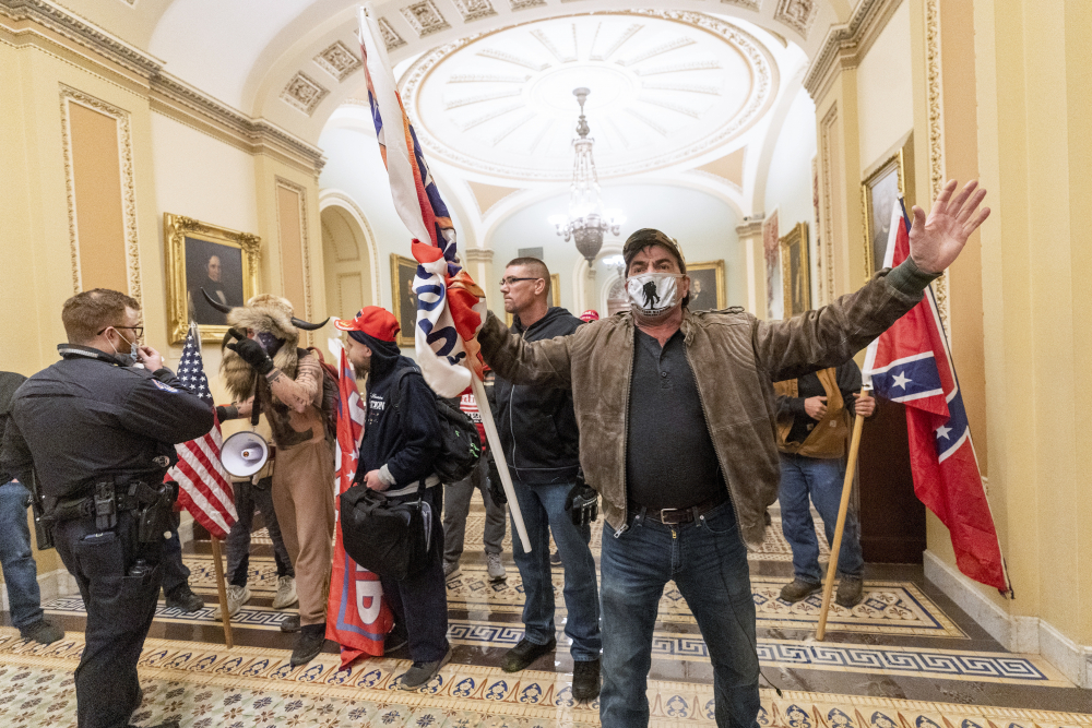 Supporters of former President Trump are confronted by U.S. Capitol Police officers outside the Senate Chamber inside the Capitol in Washington on Jan. 6. Dozens of people have been charged in connection with the riot.