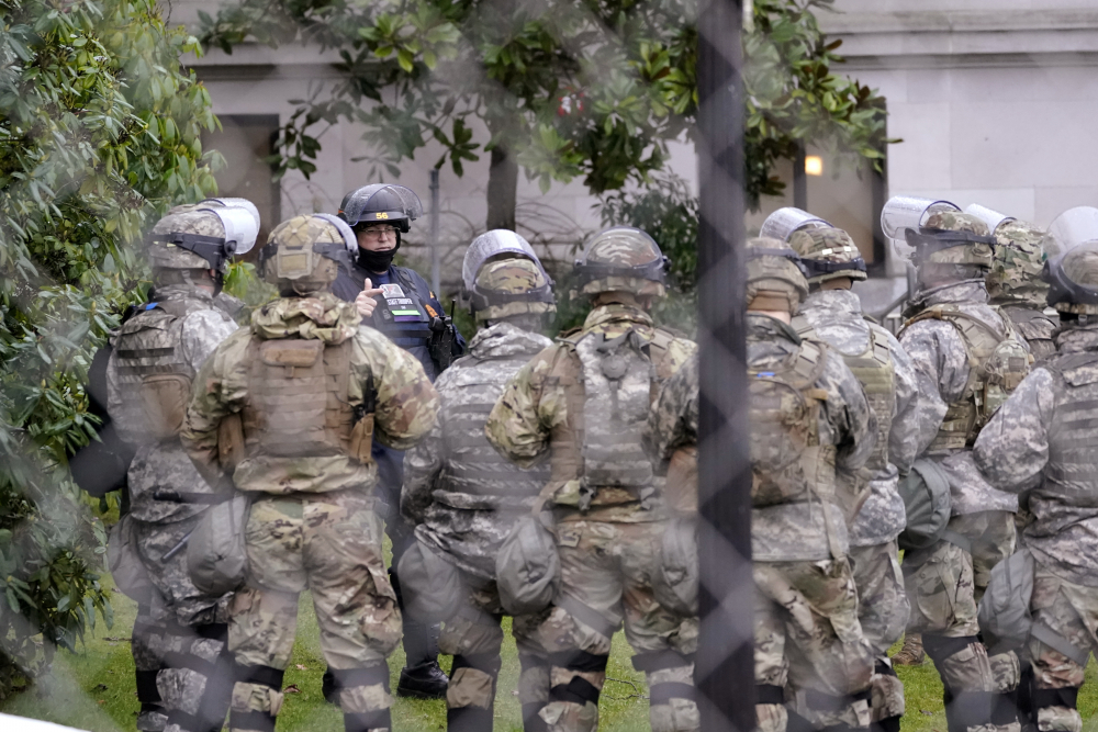 A Washington State Patrol trooper talks with members of the Washington National Guard on Monday outside the state capitol building in Olympia, Wash. State capitols across the country are under heightened security after the siege of the U.S. Capitol last week.