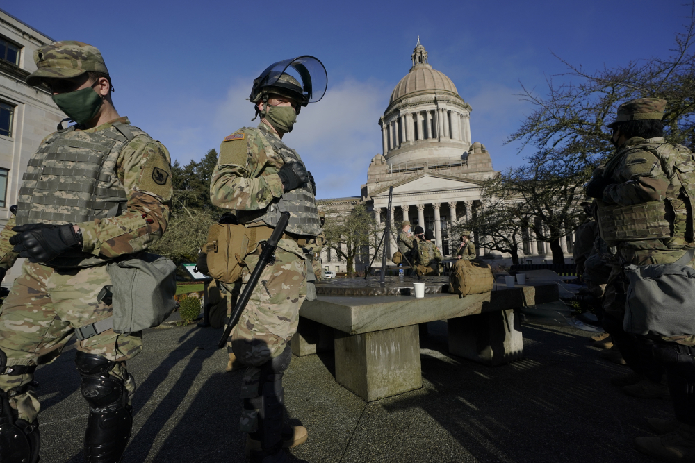 Members of the Washington National Guard stand at a sundial near the Legislative Building, Sunday, at the Capitol in Olympia, Wash.