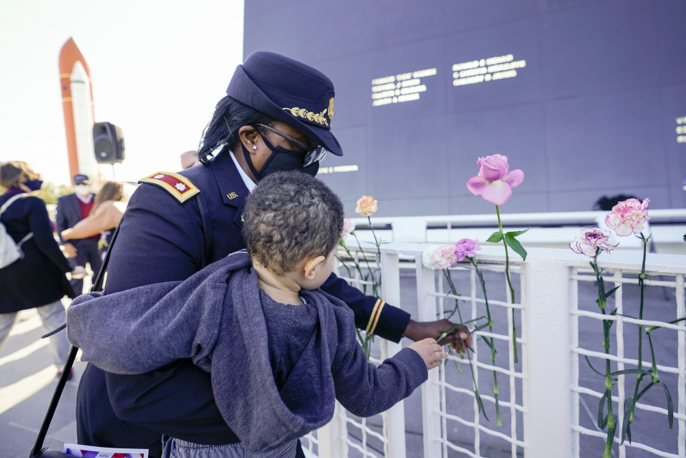 Retired Army Colonel Cynthia Watkins places a flower at the Space Mirror Memorial during a ceremony Thursday to honor fallen astronauts at the Kennedy Space Center Visitors Complex, in Cape Canaveral, Fla.